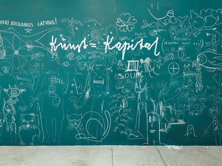 Liena Bondare, KUNST = KAPITAL, 2011, napis wykonany przy pomocy szablonu, komentarze irysunki pozostawione przezwidownię, 230 x 420 x 2 cm.