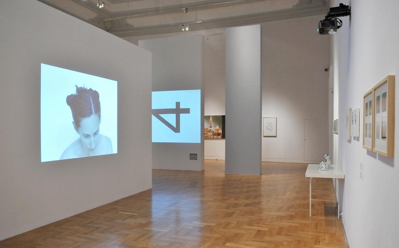Od lewej: Nelly Agassi, Assuta, 2003, wideo, dzięki uprzejmości artystki iDvir Gallery, Tel Awiw; Mirosław Bałka, IKnew It Had 4 ln It, 2008, projekcja wideo, Muzeum Szuki Nowoczesnej wWarszawie; Luc Tuymans: Perfumy, 2014 (fragment), olej, płótno, dzięki uprzejmości artysty iDavid Zwirner Gallery New York/London; Kosmetyki, 2000, olej, płótno, kolekcja prywatna