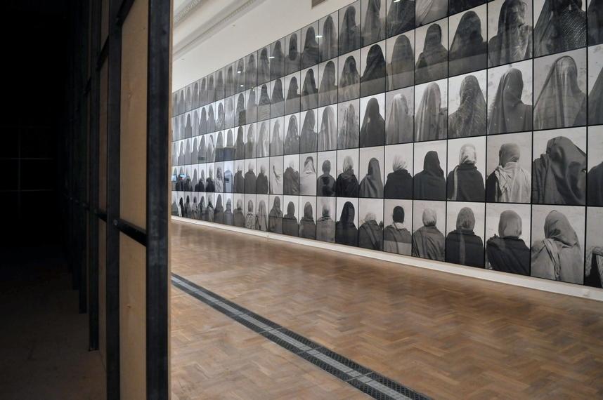 Od lewej: Mirosław Bałka, 233906250 cc, 2014, stal, sklejka, dzięki uprzejmości artysty; Santiago Sierra, 146 kobiet, 2005 (Vrindavan, Indie), 146 fotografii, instalacja, dzięki uprzejmości Studio Santiago Sierra