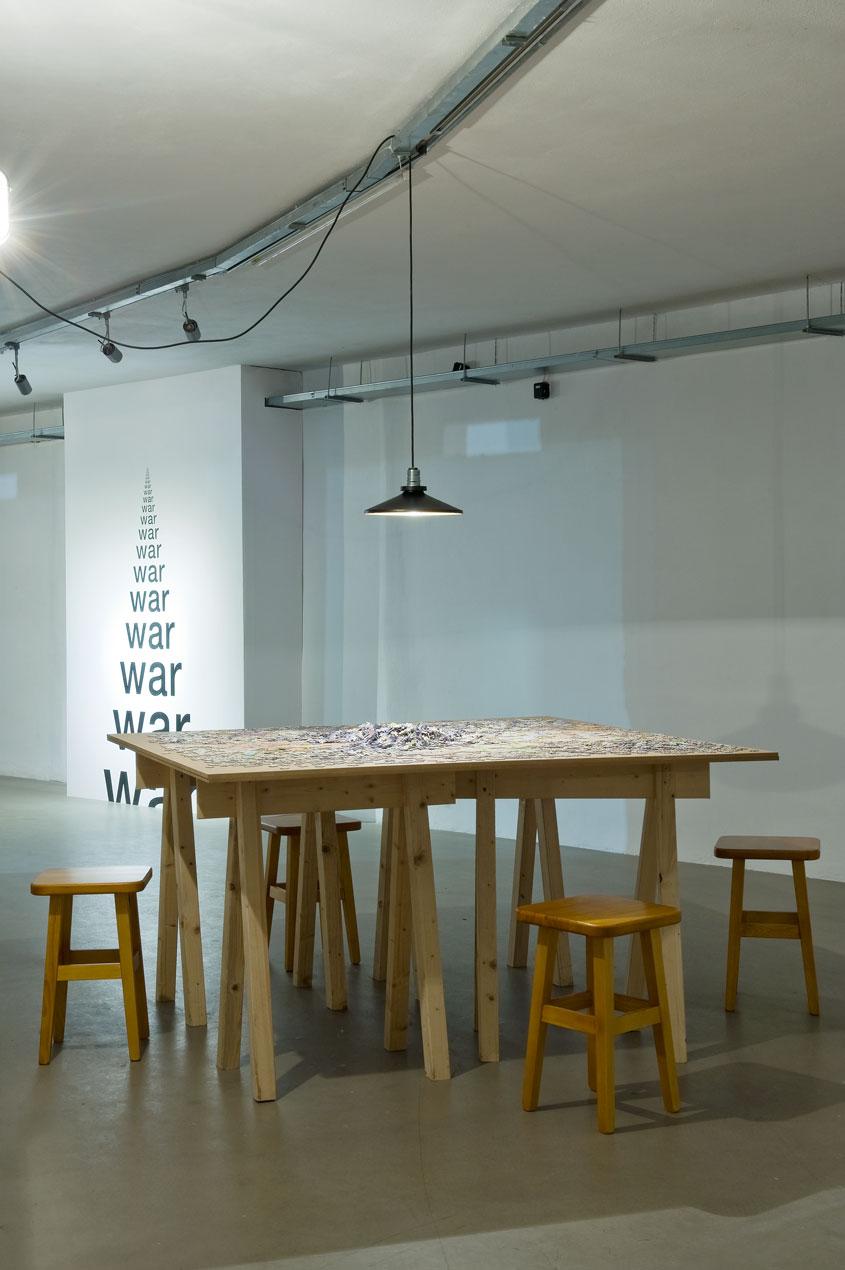 """2.Michael Merkel """"Miasto wprocesie"""", instalacja, mapy miasta, krzesła, stół, 2014. Edycja graficzna: Fabian Eggert, fot.M. Kujda"""