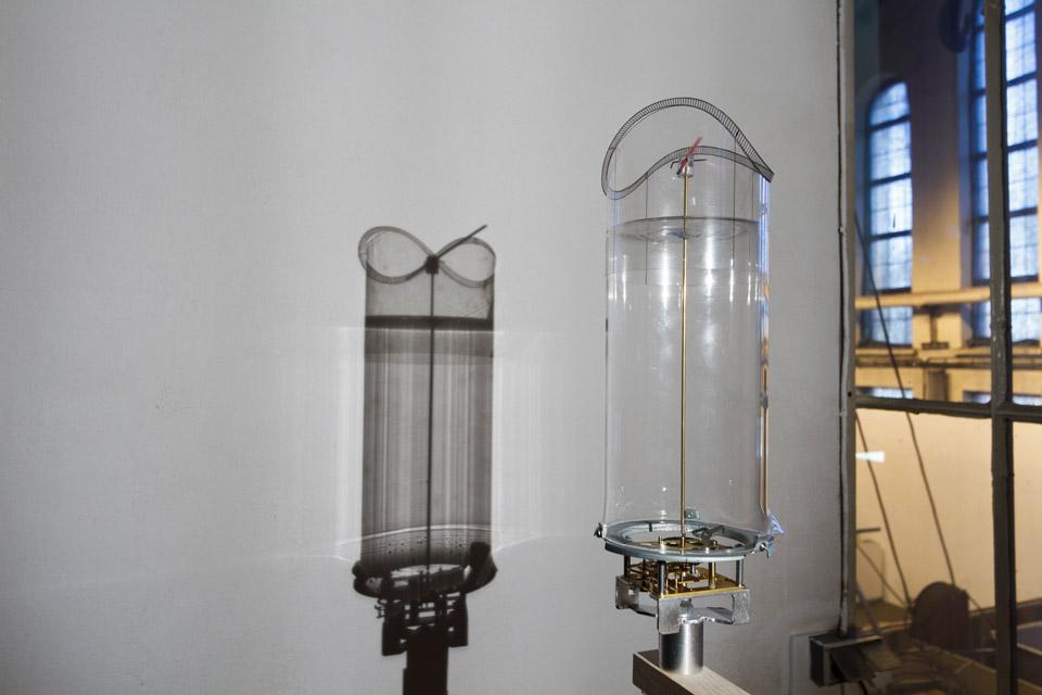 Attila Csörgő, Clock-work, 2015, zegar, statyw, lampa, szkło, folia transparentna
