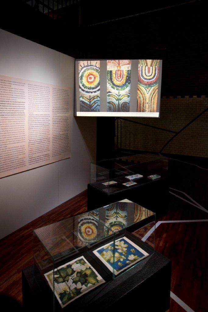 Część wystawy poświęcona malarstwu monumentalnemu. Napierwszym planie projekty malowideł ceramicznych autorstwa Anny Szpakowskiej-Kujawskiej. Naekranie mozaiki autorstwa Ewy Surowiec-Butrym.