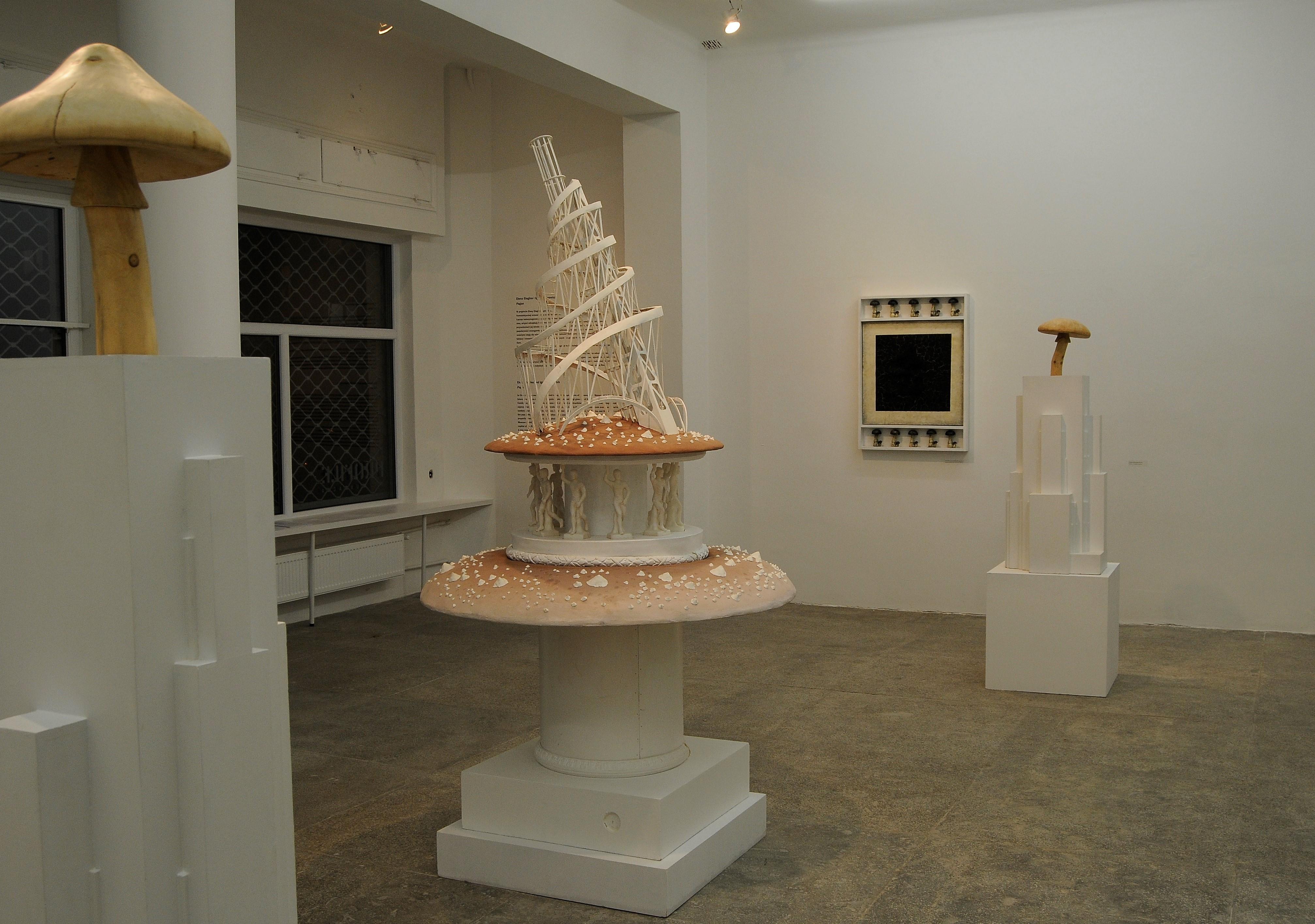 Widok wystawy Pagan. Elena Elagina & Igor Makarevich. (Odlewej) Architekton 2, 2008, Muchomor zwieżą Tatlina, 2012, Architekton 1, 2008, Czarny kwadrat zgrzybami, 2008 (naścianie)